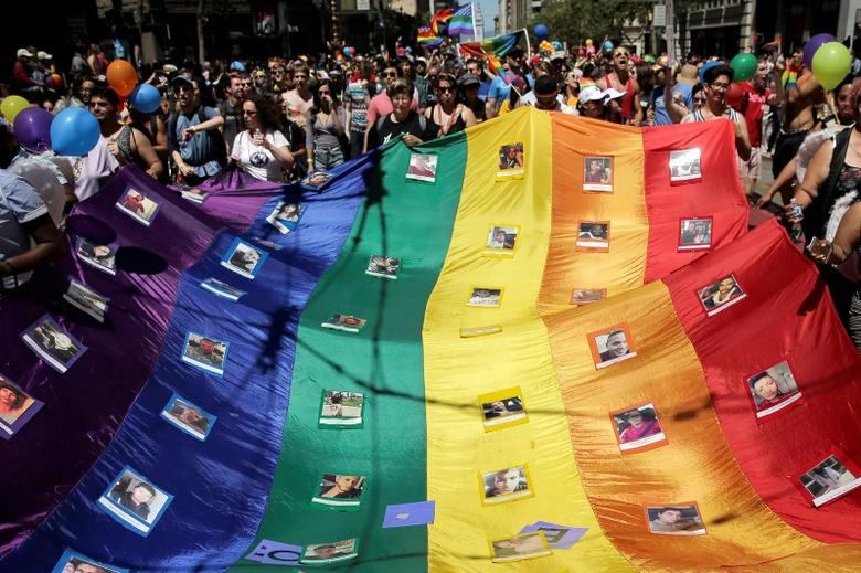 Marchers hold a rainbow flag with photos of the victims of the Orlando mass shooting during the San Francisco LGBT Pride Parade in San Francisco, California, U.S. June 26, 2016. REUTERS/Elijah Nouvelage