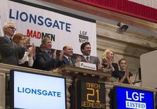 Chief Executive Officer of Lions Gate Entertainment, Jon Feltheimer (3rd L), claps with actors from the show Mad Men (L-R) John Slattery, Christina Hendricks, Jon Hamm, January Jones, and Kiernan Shipka with the show's creator Matthew Weiner (C) while visiting the New York Stock Exchange to ring the opening bell in New York, March 21, 2012.   REUTERS/Lucas Jackson