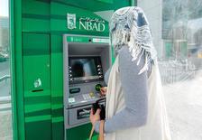 """Женщина у банкомата возле штаб-квартиры National Bank of Abu Dhabi. 3 апреля 2013 года. Советы директоров банков Абу-Даби National Bank of Abu Dhabi и First Gulf Bank в воскресенье одобрили их слияние, в результате которого будет создан финансовый """"тяжеловес"""" с объемом активов около $175 миллиардов. REUTERS/Ben Job"""