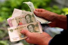 La actividad del sector de servicios de China se aceleró a un máximo de 11 meses en junio, mostró el martes un sondeo privado, distanciándose de la debilidad de las empresas manufactureras, una tendencia que de mantenerse indicaría que Pekín está logrando avances en las reformas a la economía. En la foto, una cliente cuenta billetes en un puesto de frutería en un mercado en Pekín el 9 de mayo de 2016.  REUTERS/Kim Kyung-Hoon