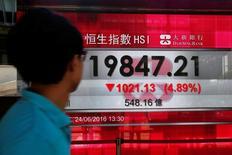 Прохожий смотрит на дисплей с показателями индекса Hang Seng в Гонконге. Китайский фондовый рынок завершил торги вторника в плюсе ввиду новых признаков ускорения активности в секторе услуг страны, а также на ожиданиях введения новых мер стимулирования экономики. REUTERS/Bobby Yip