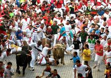 Runners fall in front of Fuente Ymbro fighting bulls near the entrance to the bullring, during the first running of the bulls at the San Fermin festival in Pamplona, northern Spain, July 7, 2016. REUTERS/Eloy Alonso