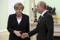 Президент России Владимир Путин (справа) протягивает руку канцлеру Германии Ангеле Меркель на встрече в московском Кремле 10 мая 2015 года. Меркель призвала к диалогу Россию, чья напористость беспокоит соседей на Западе и станет главной темой варшавского саммита НАТО в пятницу. REUTERS/Sergei Karpukhin