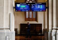 """El Ibex-35 cerró el jueves al alza por primera vez en una semana condicionada por las incertidumbres del """"brexit"""" y las dudas sobre el sector financiero en Italia y Portugal. En la imagen de archivo, un hombre camina bajo unas pantallas electrónicas en la Bolsa de Madrid.  REUTERS/Andrea Comas - RTX2HYKG"""