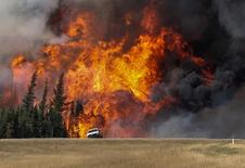 File photograph of smoke and flames from the wildfires erupting behind a car on the highway near Fort McMurray, Alberta, Canada, May 7, 2016.  REUTERS/Mark Blinch/File Photo
