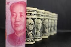 Las reservas de divisas de China subieron inesperadamente en junio en 13.400 millones de dólares a 3,21 billones de dólares, mostraron el jueves datos del banco central, rebotando desde el mínimo en cinco años que anotaron en mayo. En la imagen, un billete de 100 yuanes y billetes de un dólar en una foto ilustrativa en Pekín el 21 de enero de 2016. REUTERS/Jason Lee