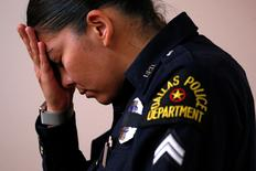 Служащая далласской полиции в ходе богослужения в память о нескольких убитых полицейских. Даллас, Техас, 10 июля 2016 года.  Прошедший Афганистан американский военный в запасе, застреливший пятерых полицейских на демонстрации в Далласе, планировал более масштабную атаку, сообщили власти, пытающиеся остудить уличные протесты. REUTERS/Carlo Allegri