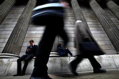 A man and woman use their mobile phones as commuters walk past the columns of the Bank of England in the City of London, July 3, 2012.  REUTERS/Andrew Winning/File Photo