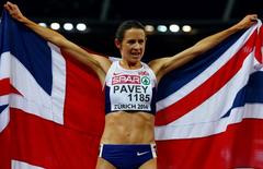 Jo Pavey of Britain holds her national flag after winning the women's 10000 metres final during the European Athletics Championships at the Letzigrund Stadium in Zurich August 12, 2014.  REUTERS/Arnd Wiegmann