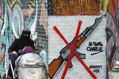 """Женщина с коляской у граффити """"Je Suis Charlie"""" в Лондоне. 14 января 2015 года. REUTERS/Luke MacGregor"""