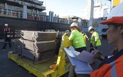 Trabajadores con un cargamento de cátodos de cobre en el puerto de Valparaíso, Chile, ene 25, 2015. La fortaleza del dólar presionó a los metales básicos, luego de que alcanzaran niveles máximos alentados por datos de crecimiento económico en China que impulsaron la confianza y dejaron la puerta abierta para más estímulos.  REUTERS/Rodrigo Garrido