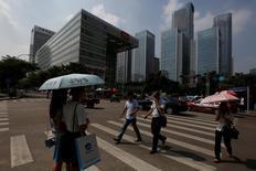 Personas cruzan una calle en el distrito de Nanshan en Shenzhen. 14 de septiembre de 2015. Los precios de las viviendas en 70 grandes ciudades en China subieron un 7,3 por ciento en junio frente al mismo mes del año previo, mostró el lunes un sondeo oficial. REUTERS/Bobby Yip