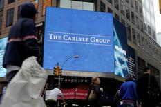 Passersby walk in front of video monitors announcing the Carlyle Group's listing on the NASDAQ market site in New York's Times Square after the opening bell for trading, U.S. May 3, 2012. REUTERS/Keith Bedford/File Photo