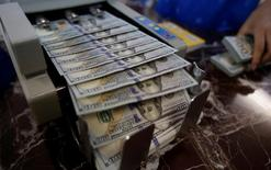 Un empleado cuenta dólares estadounidenses en una sucursal bancaria en Hanoi, Vietnam. 16 de mayo de 2016. El dólar subía frente al yen el lunes y se acercaba a máximos en tres semanas debido a que los inversores revertían operaciones en activos de refugio tras un fallido golpe de Estado en Turquía. REUTERS/Kham
