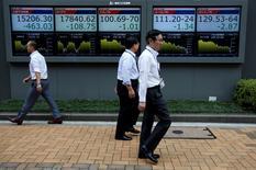 Peatones caminan delante de unas pantallas que muestran información bursátil, afuera de una correduría en Tokio, Japón.  6 de julio de 2016. Las bolsas de Asia caían el martes en momentos de que un declive en los precios del petróleo limitaba el entusiasmo por un salto de las acciones en Wall Street, lo que llevó a los inversores a recoger ganancias. REUTERS/Issei Kato