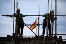 El Reino de España colocó el martes 6.000 millones de euros en un bono sindicado a 10 años a un precio de 95 puntos básicos sobre midswaps y un cupón del 1,3 por ciento. En la imagen de archivo, trabajadores en el andamio de una obra en Sevilla con la bandera de España al fondo, el 28 de abril de 2016. REUTERS/Marcelo del Pozo