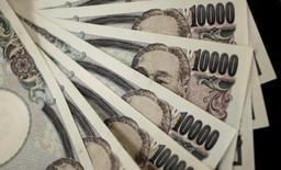"""Банкноты в 10.000 иен. Токио, 2 августа 2011 года. Иена отошла от минимумов шести недель в пятницу, после того как комментарии главы Банка Японии Харухико Куроды развеяли предположения, что Токио может готовить радикальные меры стимулирования экономики посредством так называемых """"вертолетных денег"""". REUTERS/Yuriko Nakao/File Photo"""