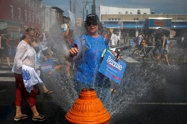 Supporters of U.S. Senator Bernie Sanders cool off with water hydrant...