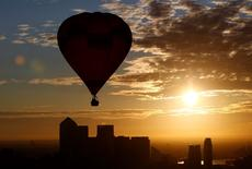 A hot air balloon rises into the early morning sky in front of the Canary Wharf financial district of London, July 25, 2011. REUTERS/Andrew Winning