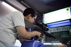 Мальчик играет в видеоигру, симулирующую военные действия. Каракас, 10 ноября 2009 года. Полиция ищет связь между жестоким расстрелом в Мюнхене на прошлой неделе и увлечением юного стрелка культивирующими насилие видеоиграми. REUTERS/Carlos Garcia Rawlins