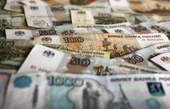 Рублевые купюры. Рубль снижается в начале биржевых торгов вторника на фоне дешевой нефти и после прохождения накануне пика налогов, но при этом локальная продажа экспортной выручки может проявляться к уплате в четверг налога на прибыль и к выплате дивидендов, что будет сдерживать ослабление российской валюты. REUTERS/Kacper Pempel