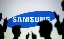 Люди на фоне логотипа Samsung. Технологический гигант Samsung Electronics Co Ltd сообщил в четверг, что ожидает стабильно высокую прибыль во втором полугодии 2016 года, при этом хороший спрос на компоненты, вероятно, компенсирует повышенное давление на маржу прибыли от смартфонов.  REUTERS/Dado Ruvic/Illustration/File Photo