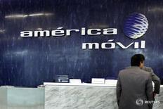 El logo de América Móvil es visto en la pared del área de recepción de las oficinas corporativas de la empresa en Ciudad de México, 13 de febrero de 2013. El gigante mexicano de telecomunicaciones América Móvil reportó el jueves una caída mayor a la esperada en su utilidad neta del segundo trimestre, presionada principalmente por menores ingresos en México, donde enfrenta regulaciones más estrictas. REUTERS/Edgard Garrido