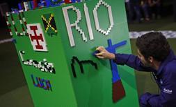 Homem usa tijolo de Lego para montar placa com símbolos do Rio de Janeiro durante apresentação de uma maquete da cidade feita de Lego no Centro de Mídia do Rio 01/08/2016 REUTERS/Nacho Doce