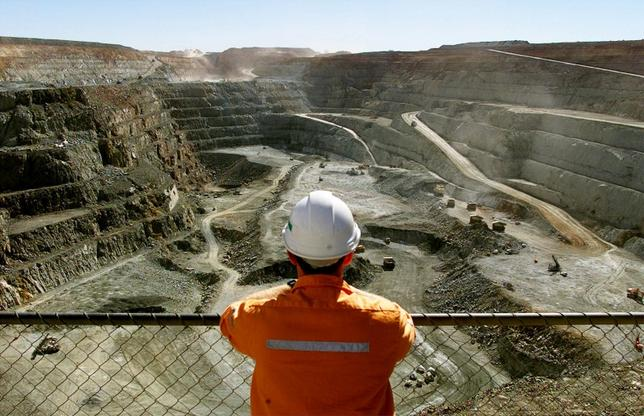 A miner looks across the largest open pit gold mine in Australia called the Fimiston Open Pit, also known as the Super Pit, in the gold-mining town of Kalgoorlie, located around 500 kilometres east of Perth July 27, 2001.     REUTERS/David Gray/File photo