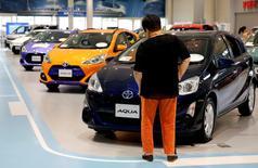 Toyota Motor Corp recortó su proyección para el beneficio operativo del conjunto del ejercicio lpor un impacto más duro de la fortaleza del yen en su cuenta de resultados. En la foto, un visitante mira a un modelo híbrido de Toyota en  la exposición del fabircante de coches en Tokio el 14 de junio de 2016.    REUTERS/Toru Hanai