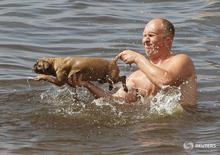 Мужчина купает собаку в Волге в Конаково 18 июля 2010 года. Выходные в Москве будут жаркими, свидетельствует усреднённый прогноз, составленный на основании данных Гидрометцентра России, сайтов intellicast.com и gismeteo.ru. REUTERS/Denis Sinyakov