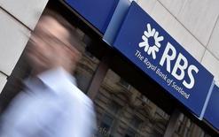 El grupo financiero Royal Bank of Scotland no es capaz de despedirse de los números rojos. La entidad dijo el viernes que las pérdidas netas en el primer semestre sumaron 2.050 millones de libras frente a un saldo negativo de 179 millones hace un año. En la imagen de archivo, un hombre camina junto a una sucursal del RBS en Londres. REUTERS/Toby Melville/File Photo
