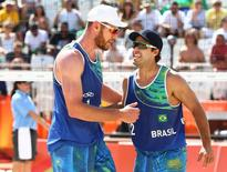2016 Rio Olympics - Beach Volleyball - Men's Preliminary - Beach Volleyball Arena - Rio de Janeiro, Brazil - 06/08/2016. Alison (BRA) of Brazil and Bruno Oscar Schmidt (BRA) of Brazil react. REUTERS/Ruben Sprich