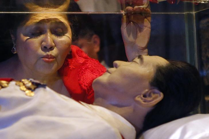 Former first lady Imelda Marcos kisses the glass coffin of her husband, late president Ferdinand Marcos, who remains unburied since his death in 1989, during her 85th birthday celebration in Ferdinand Marcos' hometown of Batac, Ilocos Norte province, in northern Philippines July 2, 2014. REUTERS/Erik De Castro