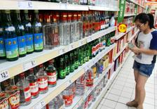 A woman holds a bottle of alcohol product at a supermarket in Nanjing, Jiangsu Province, China, August 6, 2016. Picture taken August 6, 2016. China Daily/via REUTERS