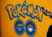 Homem usa celular em frente a uma propaganda do jogo Pokémon Go em Tóquio, no Japão 27/07/2016 REUTERS/Kim Kyung-Hoon/File Photo