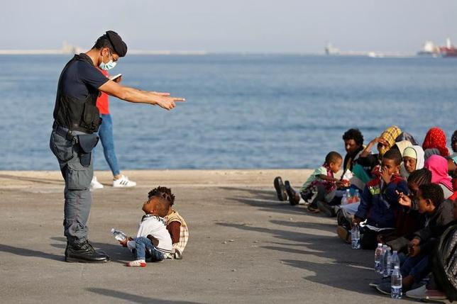 A policeman talks with children as migrants disembark from Migrant Offshore Aid Station (MOAS) ship Topaz Responder in the Sicilian harbour of Augusta, Italy June 30, 2016. REUTERS/Antonio Parrinello