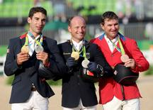 2016 Rio Olympics - Equestrian - Victory Ceremony - Eventing Individual Victory Ceremony - Olympic Equestrian Centre - Rio de Janeiro, Brazil - 09/08/2016. Astier Nicolas (FRA) of France, Michael Jung (GER) of Germany and Phillip Dutton (USA) of USA celebrate their medals. REUTERS/Tony Gentile