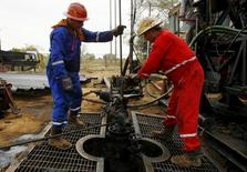Unos trabajadores en un pozo petrolero en Lagunillas, Venezuela, mar 18, 2015. La producción de crudo venezolana retrocedió 0,25 por ciento en junio respecto al mes previo, ubicándose en 2,364 millones de barriles por día (bpd), según datos del país hechos públicos el miércoles por la Organización de Países Exportadores de Petróleo (OPEP).   REUTERS/Isaac Urrutia