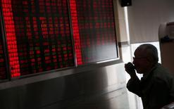 Un hombre frente a una pantalla que muestra información bursátil, en una correduría en Pekín, China. 27 de junio de 2016. El índice de acciones líderes de China CSI300 cerró el viernes en su nivel más alto en siete meses, impulsado por títulos financieros e inmobiliarios, después de que datos económicos decepcionantes plantearon la posibilidad de más estímulos gubernamentales. REUTERS/Kim Kyung-Hoon
