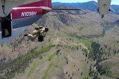 A smokejumper leaps from an airplane during a training flight above Winthrop, Washington, U.S.,  June 30, 2016. REUTERS/David Ryder