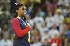 2016 Rio Olympics - Artistic Gymnastics - Victory Ceremony - Women's Vault Victory Ceremony - Rio Olympic Arena - Rio de Janeiro, Brazil - 14/08/2016. Simone Biles (USA) of USA sings her national anthem with her gold medal on the podium.    REUTERS/Mike Blake