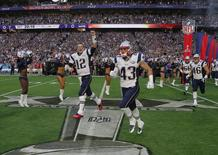 New England Patriots quarterback Tom Brady (12) runs out onto the field with teammates Nate Ebner (43), James Develin (46) and the rest of his team ahead of the start of the NFL Super Bowl XLIX football game against the Seattle Seahawks in Glendale, Arizona February 1, 2015. REUTERS/Brian Snyder