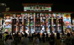 People watch a light show for 30 day countdown of the upcoming G20 Summit in Hangzhou, Zhejiang Province, China, August 5, 2016. Picture taken August 5, 2016. REUTERS/Stringer