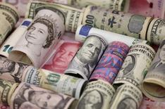 Банкноты разных стран. Доллар занял оборонительную позицию на торгах понедельника, испытывая давление со стороны пессимистичных данных из США, которые умерили ожидания инвесторов в отношении скорого подъема ставок ФРС.  REUTERS/Jason Lee/Illustration/File Photo
