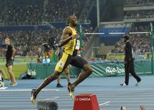 Усэйн Болт после забега на 100 метров. В течение блистательных 9,81 секунды в воскресенье все беды легкой атлетики отошли на второй план, когда Усэйн Болт мчался к победе в беге на 100 метров, чтобы стать первым легкоатлетом, сумевшим выиграть стометровку на трех Олимпиадах кряду. REUTERS/Rickey Rogers