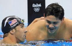 Michael Phelps of the U.S. congratulates Joseph Schooling of Singapore after Schooling won the gold in the 100m butterfly. REUTERS/Dominic Ebenbichler