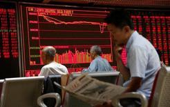 Un hombre lee un diario frente a una pantalla que muestra información bursátil en una correduría en Pekín, China. 27 de junio de 2016. Las acciones chinas se alejaron el martes desde unos máximos en siete meses luego de que una fuerte corrección en los papeles de los bancos contrarrestó la fortaleza en el sector inmobiliario. REUTERS/Kim Kyung-Hoon