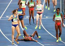 2016 Rio Olympics - Athletics - Final - Women's 1500m Final - Olympic Stadium - Rio de Janeiro, Brazil - 16/08/2016. Faith Chepngetich Kipyegon (KEN) of Kenya falls after winning the final. REUTERS/David Gray