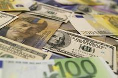 Банкноты доллара США, евро и швейцарского франка в отделении банка в Будапеште. 8 августа 2011 года. Объем золотовалютных резервов РФ составил $395,7 миллиарда на конец прошлой недели, и они ушли с максимума 1 года и 8 месяцев года из-за переоценки валют и активов, входящих в структуру резервов. REUTERS/Bernadett Szabo